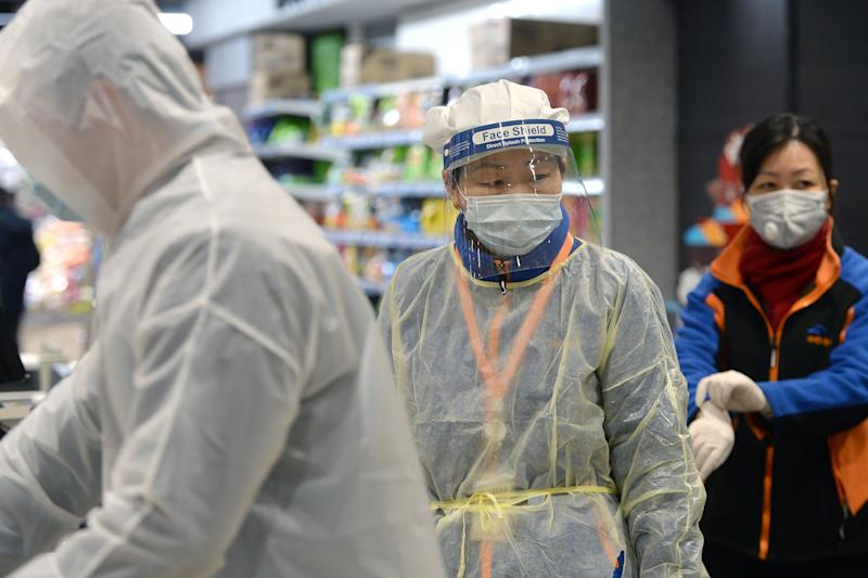 A staff member wearing a protective mask and suit works at a supermarket in Wuhan, the epicentre of the outbreak of a novel coronavirus, in China's central Hubei province. - The death toll from the novel coronavirus surged past 900 in mainland China on February 10, overtaking global fatalities in the 2002-03 SARS epidemic, even as the World Health Organization said the outbreak appeared to be stabilising. (Photo by STR / AFP) / China OUT (Photo by STR/AFP via Getty Images)