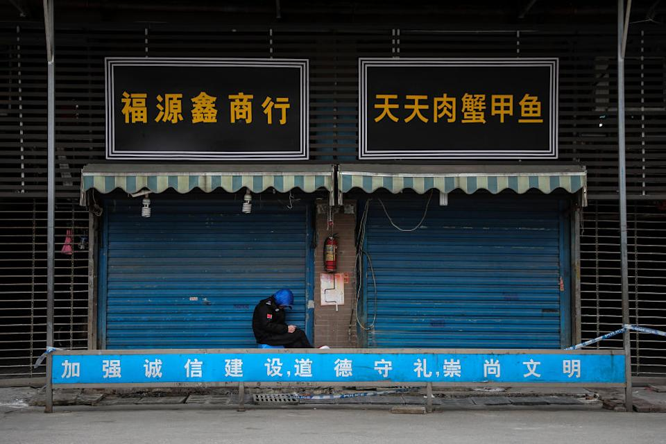 A security guard sits outside the closed Huanan Seafood Wholesale Market, which has been linked to cases of Coronavirus.