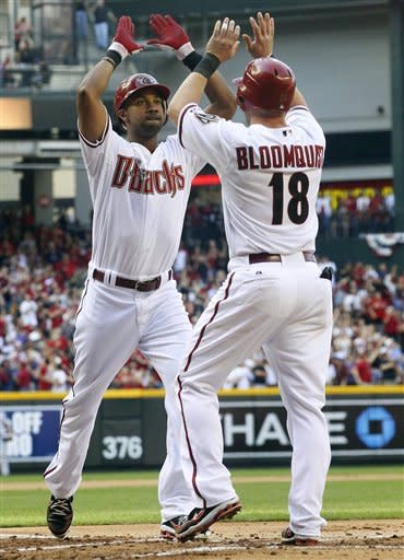 Arizona Diamondbacks' Chris Young high-fives Willie Bloomquist (18) after Young hit a two-run home run in the first inning of an opening day baseball game against the San Francisco Giants, Friday, April 6, 2012, in Phoenix. (AP Photo/Matt York)