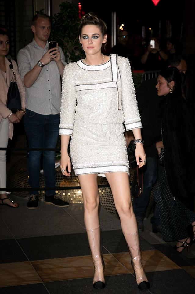 <p>Arriving at the Chanel and <em>Vanity Fair France</em> party, Kristen Stewart took her hemline shorter by wearing a mini dress by Chanel paired with the brand's iconic plastic boots. (Photo: Getty) </p>