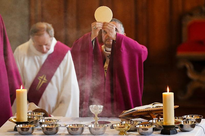Archbishop Dominique Lebrun (C) celebrates a special penitential mass on October 2, 2016, to mark the re-opening of the Saint-Etienne-du-Rouvray church and to pay tribute to Father Jacques Hamel
