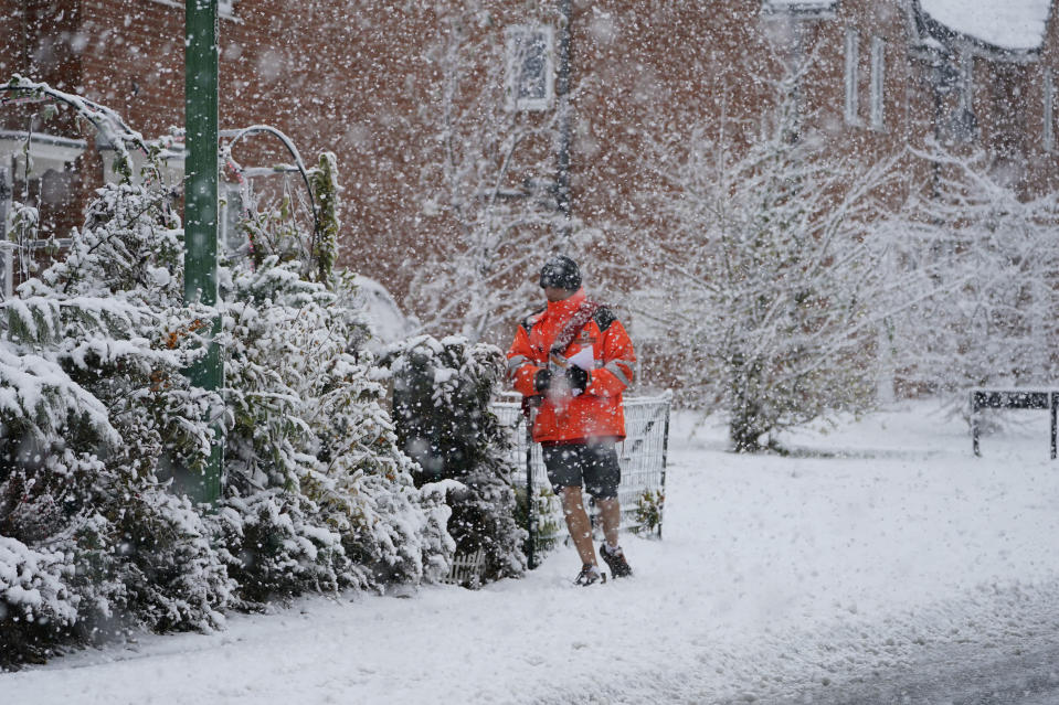 <p>A Royal Mail worker wearing shorts battles through the snow in County Durham </p>