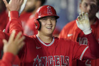 Los Angeles Angels' Shohei Ohtani is greeted in the dugout after he hit a solo home run during the first inning of a baseball game against the Seattle Mariners, Sunday, Oct. 3, 2021, in Seattle. (AP Photo/Ted S. Warren)