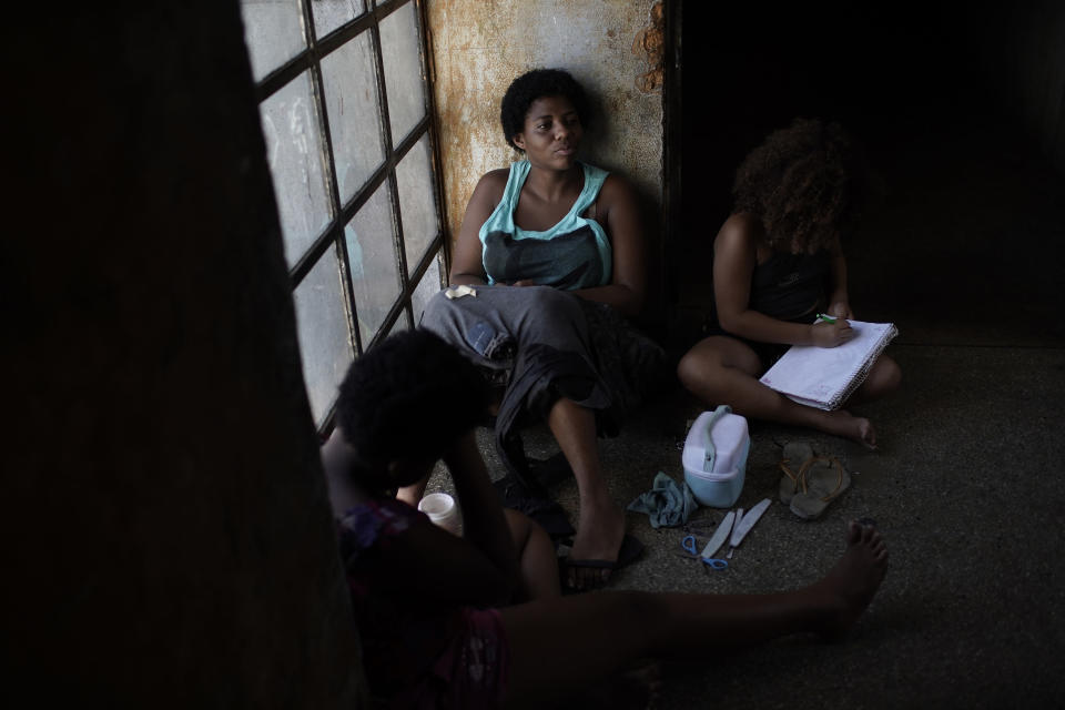 A mother sits on a window seat as she accompanies her daughter inside an occupied building where they live, in Rio de Janeiro, Brazil, Thursday, March 11, 2021. Brazilian women face worse labor choices or require flexible hours to raise their children, particularly since public schools provide only half days of classes. (AP Photo/Silvia Izquierdo)