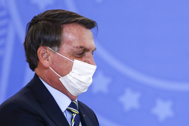 Brazilian President Jair Bolsonaro gestures as he wears a facemask during an official ceremony at the presidential office in Brasilia, on June 17, 2020. (Photo by Sergio LIMA / AFP) (Photo by SERGIO LIMA/AFP via Getty Images)
