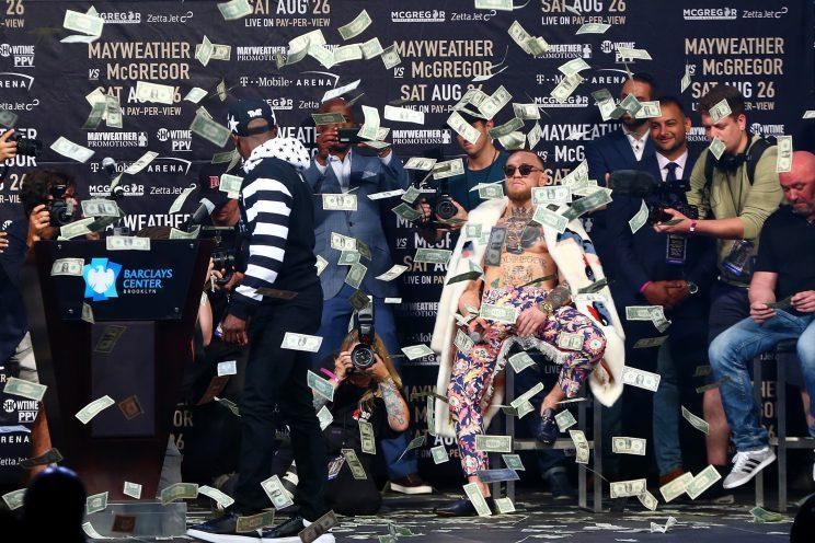 Floyd Mayweather (L) showered Conor McGregor in $1 bills in a bizarre and awkward news conference Thursday. (Getty)