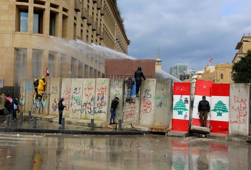 FILE PHOTO: Demonstrators are sprayed with a water cannon during a protest seeking to prevent MPs and government officials from reaching the parliament for a vote of confidence, in Beirut