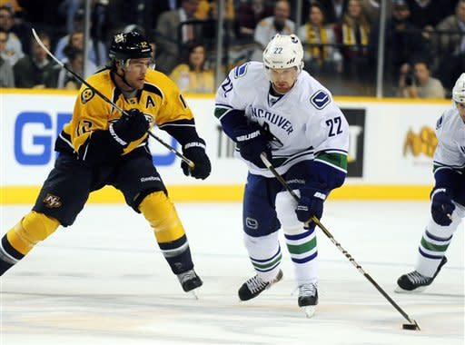 Vancouver Canucks left wing Daniel Sedin (22), of Sweden, skates past Nashville Predators center Mike Fisher (12) in the first period of an NHL hockey game on Tuesday, Feb. 7, 2012, in Nashville, Tenn. (AP Photo/Mike Strasinger)