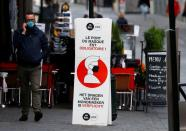 A man walks past a sign announcing the mandatory use of masks amid the coronavirus disease outbreak in Brussels