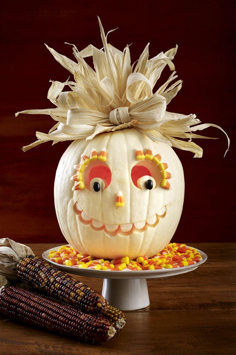 "<p>With highlighter, draw curved line on white pumpkin for mouth; add half-circles below for teeth. Carve along bottom of teeth, widening as needed. Using linoleum cutter, etch away skin on teeth. </p><p>Carve eyes, then hot-glue 2 black jelly beans as pupils. Hot-glue <span class=""redactor-unlink"">candy corn</span> nose and eyelashes. For hair, dip dried <span class=""redactor-unlink"">corn husks</span> (from a grocery store) in a bowl of water and lay them out. While still damp, tear into different-width strips. </p><p>To make curly pieces, roll a few and secure with paper clips until dry. Working around stem, hot-glue one end of each husk strip to top of pumpkin; use straight pins to secure as needed. Fold 2 wider corn husk strips in half, and wrap together at ends with a third strip to form a bow; hot-glue in place.</p><p><strong>What You'll Need</strong>: <a href=""https://www.amazon.com/dp/B01J9S3Z0A/ref=dp_cerb_1"" rel=""nofollow noopener"" target=""_blank"" data-ylk=""slk:Linoleum cutter"" class=""link rapid-noclick-resp"">Linoleum cutter</a> ($8, Amazon)</p>"