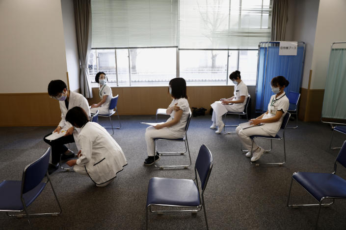 FILE - In this Feb. 17, 2021, file photo, medical workers wait for consultation after receiving a dose of the COVID-19 vaccine at Tokyo Medical Center in Tokyo. Frustration is mounting over Japanese Prime Minister Yoshihide Suga's request that people cooperate while he pushes to hold the Olympics in just over two months. (Behrouz Mehri/Pool Photo via AP, File)