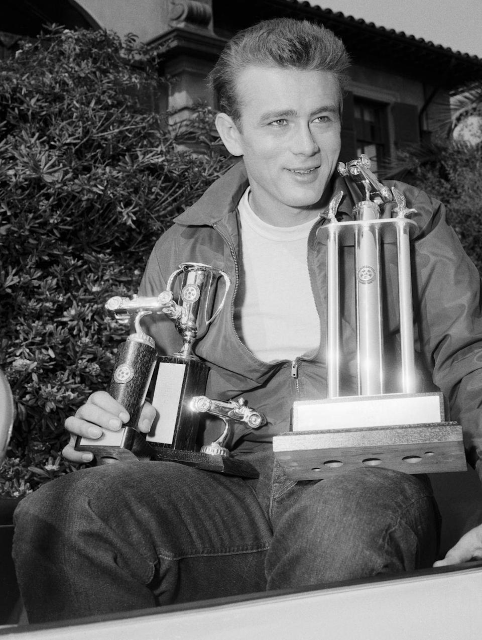 <p>Actor James Dean (<em>Rebel Without A Cause</em>) proudly poses with the three trophies he took home for winning the Palm Springs Road Race on May 6, 1955. The 24-year-old car enthusiast tragically died in a vehicle-related accident that following September.<br></p>
