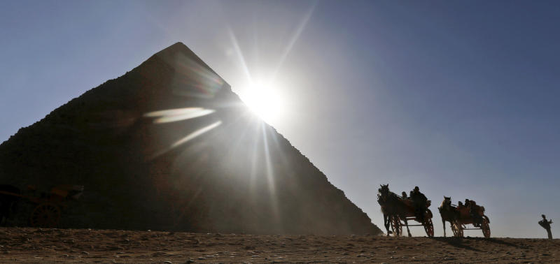 FILE - In this Wednesday, Dec. 12, 2012 file photo, Tourists ride in horse carriages past one of the Great Pyramids in Giza, Egypt. The past month saw a drop in tourists to Egypt, scared off by scenes of protests and clashes over the constitution, in new pain to a crucial industry gutted the past two years by turmoil. Tourism workers worry things won't get any better even now that the charter has been passed: Egypt's power struggles threaten to erupt into more unrest at any time, and some fear Islamists will eventually try to rein in alcohol and beach tourism. (AP Photo/Petr David Josek, File)