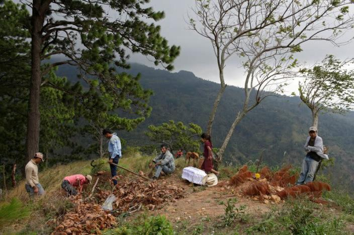Relatives of late Yesmin Anayeli dig up a grave for her burial at a hilltop in La Palmilla