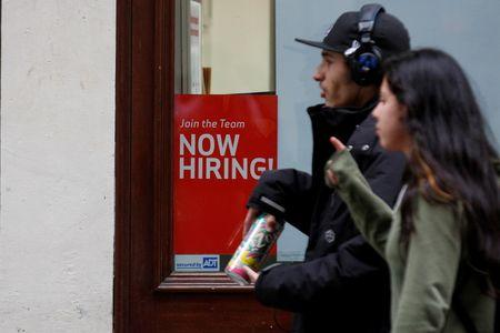 """People walk past a """"Now Hiring"""" sign in Manhattan in New York"""