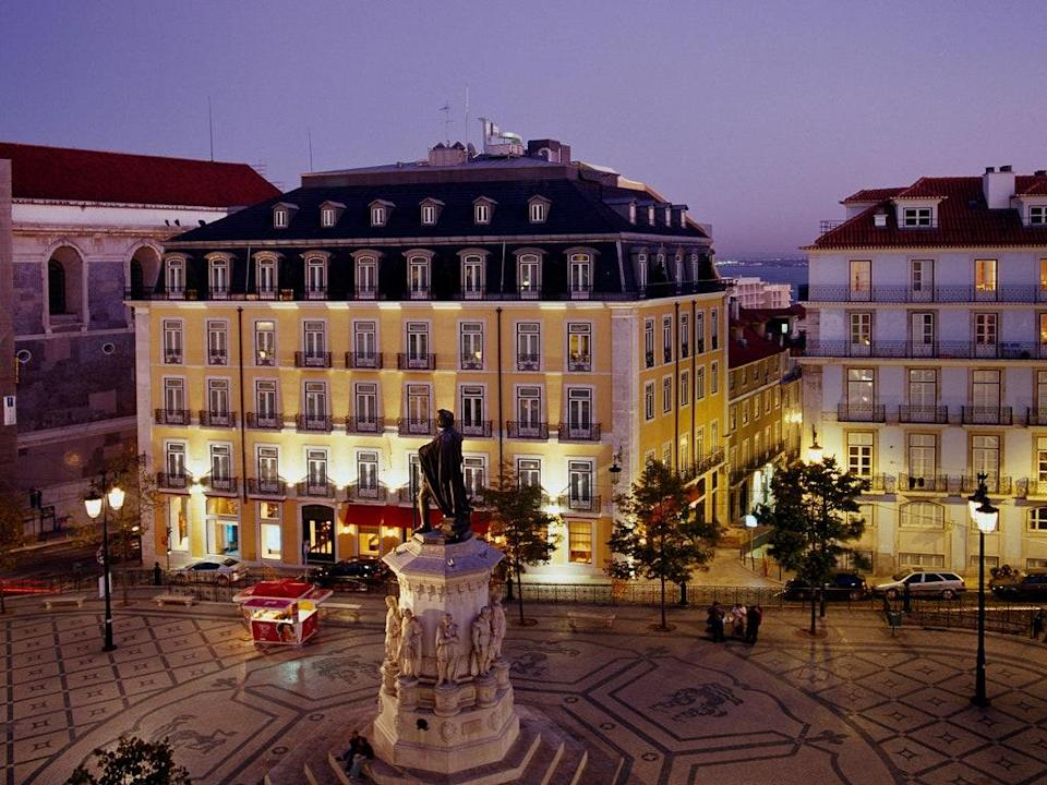"""<p><strong>Set the scene.</strong> The distinctive, primrose yellow exterior of the 18th-century building that houses the Bairro Alto Hotel has an impressive perch on the edge of Chiado's landmark square, the Praça Luís de Camões, in one of <a href=""""https://www.cntraveler.com/destinations/lisbon?mbid=synd_yahoo_rss"""" rel=""""nofollow noopener"""" target=""""_blank"""" data-ylk=""""slk:Lisbon's"""" class=""""link rapid-noclick-resp"""">Lisbon's</a> most sought-after neighborhoods. Its recent revival is rooted in the architectural heritage of the buildings, so the aim was to renew and refresh rather than to radically reinvent. There are smart terrazzo floors, a soothing palette of greys, greens, pink, rusts, and whites, and specially commissioned pieces from Portuguese artists like Vasco Araújo and Rui Chafes.</p> <p><strong>What's the backstory?</strong> First opened in 2005, before Lisbon became one of Europe's hot spots, Bairro Alto was arguably one of the city's first boutique hotels. It reopened in 2019 following a three-year renovation. The original team reunited for the re-boot, which included the Pritzker Prize winner, Eduardo Souto de Moura, who was a regular guest in its previous incarnation.</p> <p><strong>What can we expect in our rooms?</strong> The hotel is larger and now spans four Pombal-era buildings, so no two rooms are the same. The original design team, Atelier Bastir, did the public spaces and guestrooms, and each one is an elegant assemblage of antique and contemporary furniture, thoughtful touches of tradition with glazed tiles, woven fabrics, rattan, ceramics, and art by Portuguese makers. Special mention goes to the soundproofed windows, which block out the rumble of the city's yellow trams as they pass.</p> <p>__How about the food and drink? __ London-based Portuguese chef Nuno Mendes was called upon to reinvent the hotel's F&B. The fifth-floor BAHR with its open kitchen showcases his distinctive flavor combinations with plates like prawn rissoles (a Portuguese snack"""