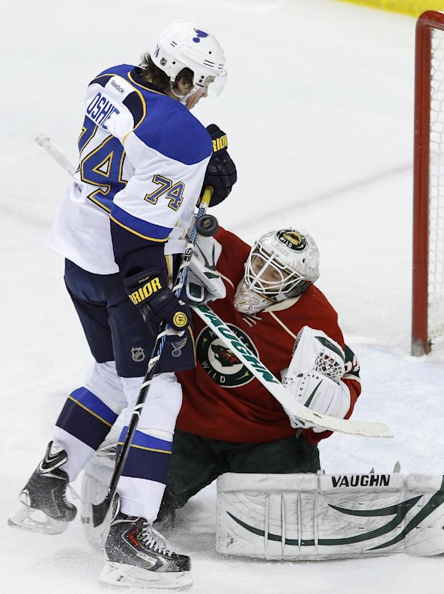 A shot goes wide past Minnesota Wild goalie John Curry, right, and St. Louis Blues right wing T.J. Oshie (74) during the first period of an NHL hockey game in St. Paul, Minn., Thursday, April 10, 2014. (AP Photo/Ann Heisenfelt)