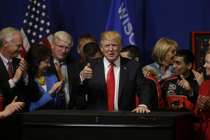 President Donald Trump gives a thumbs-up after signing an executive order to tighten the rules for technology companies seeking to bring highly skilled foreign workers to the U.S., Tuesday, April 18, 2017, at Snap-On Tools in Kenosha, Wis. (AP Photo/Kiichiro Sato)