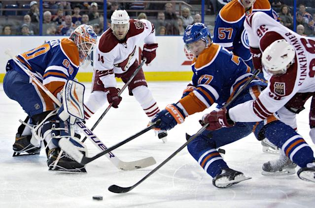 Phoenix Coyotes' Rob Klinkhammer (36) and Jeff Halpern (14) vie for the puck with Edmonton Oilers' Anton Belov (77) as goalie Ilya Bryzgalov (80) makes a save during the first period of an NHL hockey game Friday, Jan. 24, 2014, in Edmonton, Alberta. (AP Photo/The Canadian Press, Jason Franson)