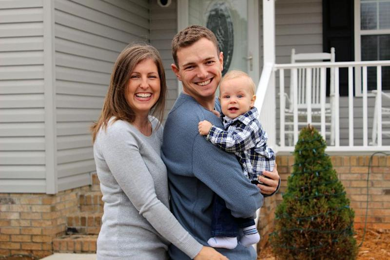 This Dec. 7, 2013 photo released by The Williamson family shows, from left, Tricia Williamson, her husband Mike Williamson, and their one-year-old son Adam at their home in Liberty, N.C. Tricia Williamson, 30, in Liberty, N.C., quit her job as an editor and producer at a TV station after crunching the numbers and realizing her salary after the birth of her son a year ago would go primarily to her commuting and child care expenses. (AP Photo/Rick Williamson)