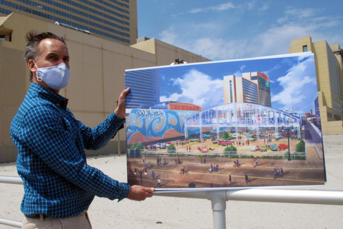 Martin Sizmur, who is in charge of construction for Philadelphia developer Bart Blatstein, shows an illustration of an 8,000-seat domed concert hall to be built next to the Showboat casino, Wednesday, April 21, 2021, in Atlantic City, N.J. Philadelphia developer Bart Blatstein is spending nearly $130 million on attractions at the former Atlantic City casino including an indoor water park; a retractible domed concert hall, a beer garden and a Boardwalk sun deck to increase family entertainment options in Atlantic City. (AP Photo/Wayne Parry)