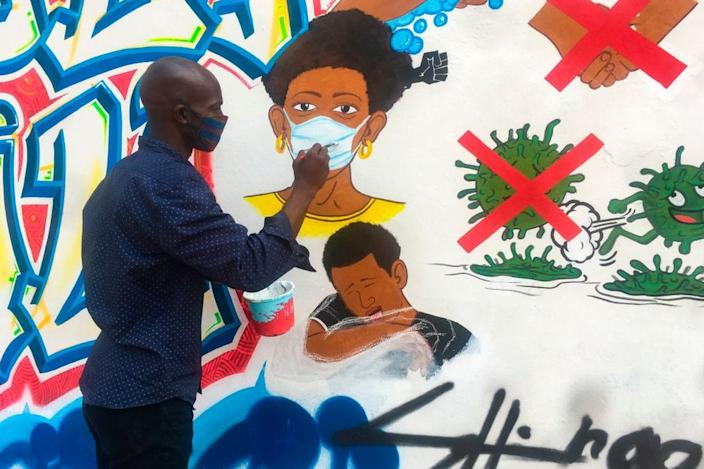 Congolese artist Chris Shongo paints a mural in Kinshasa.