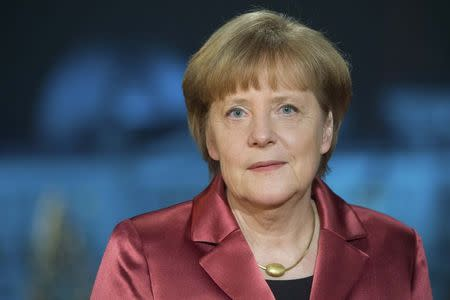 Merkel poses after recording her New Year's speech in the Chancellery in Berlin