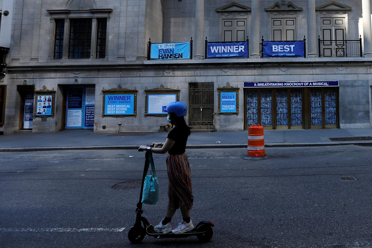 "A woman rides a scooter past the shuttered Music Box Theatre, home of the popular musical ""Dear Evan Hansen"" after industry group the Broadway League said Broadway theaters will remain closed through January 3, 2021, in New York, U.S., July 2, 2020. REUTERS/Mike Segar     TPX IMAGES OF THE DAY"