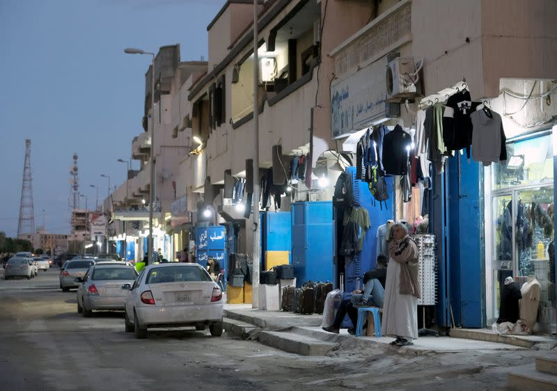 A man stands in front of a clothing store in the city of Sirte