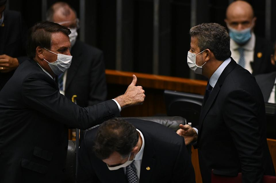 Brazil's President Jair Bolsonaro,  next to President of Brazil's Senate Rodrigo Pacheco, greets the President of Brazil's Lower House Arthur Lira attend the opening session of the Legislative Year at the National Congress in Brasilia, Brazil February 3, 2021. (Photo by Andre Borges/NurPhoto via Getty Images)