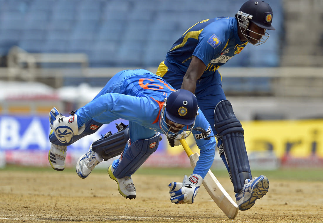 Indian wicketkeeper Dinesh Karthik (L) fields a ball as Sri Lankan cricket team captain  Angelo Mathews takes a run during the third match of the Tri-Nation series between India and Sri Lanka at the Sabina Park stadium in Kingston on July 2, 2013. Indian won the toss and elected to filed first. AFP PHOTO/Jewel Samad