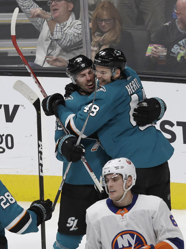 San Jose Sharks center Logan Couture, left, is congratulated by center Tomas Hertl (48), from the Czech Republic, after scoring a goal against the New York Islanders during the third period of an NHL hockey game in San Jose, Calif., Saturday, Oct. 20, 2018. The Sharks won 4-1. (AP Photo/Jeff Chiu)