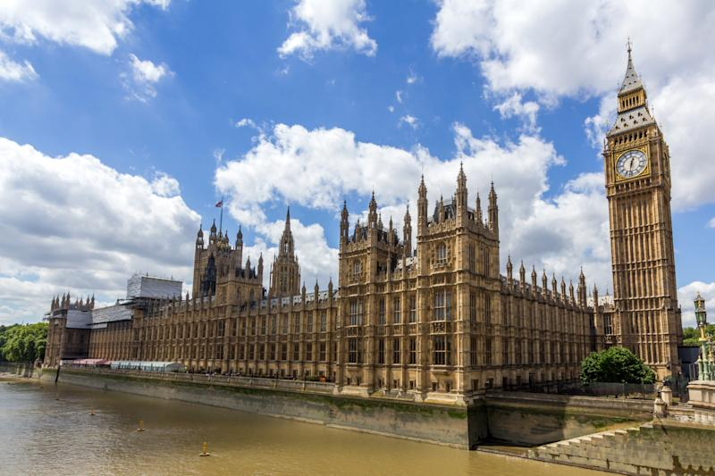 House of Commons and Palace of Westminster next to Thames river in London.