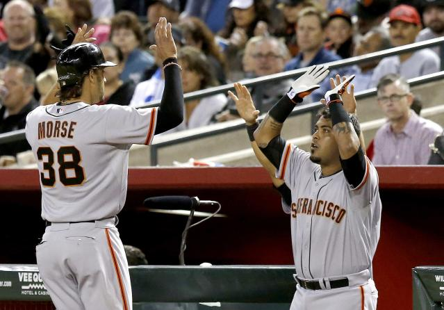 San Francisco Giants' Michael Morse (38) celebrates his RBI double with Hector Sanchez, right, during the sixth inning of a baseball game against the Arizona Diamondbacks, Wednesday, April 2, 2014, in Phoenix. (AP Photo/Ross D. Franklin)