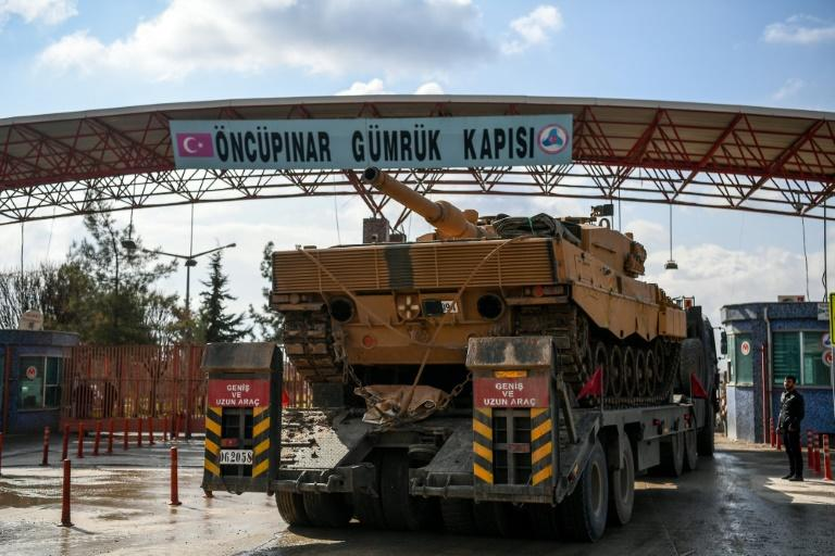 A Turkish army truck carrying a tank drives through the Oncupinar border crossing, close to the Turkish town of Kilis, in January 2018, as troops enter Syria