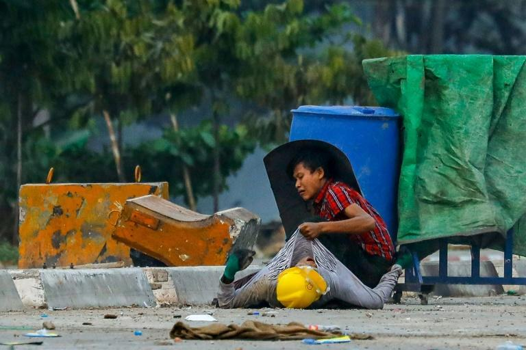 A protester uses a cut-out trash can as a shield as he attends to a demonstrator wounded when security forces opened fire in Yangon's Hlaing Tharyar township on March 14, 2021