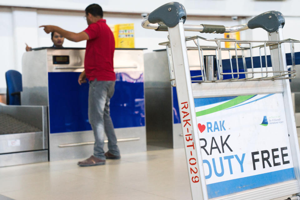 A man speaks to a check-in counter employee at the Ras al-Khaimah International Airport in Ras al-Khaimah, United Arab Emirates, Wednesday, Oct. 23, 2019. India's low-cost airline SpiceJet announced plans Wednesday to build its first international hub in the United Arab Emirates, offering a pledge of support to Boeing Co. by saying it would use now-grounded 737 MAX aircraft in the operation once regulators approve the planes for flight. (AP Photo/Jon Gambrell)
