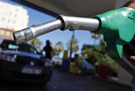 A customer uses a petrol nozzle to fill up his tank in a gas station in Nice
