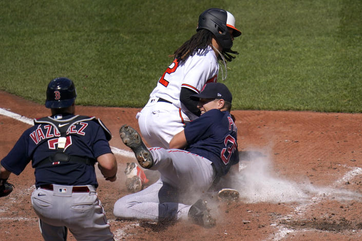 Boston Red Sox starting pitcher Nick Pivetta, right, tags out Baltimore Orioles' Freddy Galvis, center, trying to score on a wild pitch as catcher Christian Vazquez looks on during the third inning of a baseball game, Sunday, April 11, 2021, in Baltimore. (AP Photo/Julio Cortez)