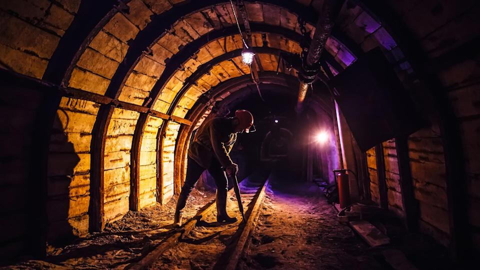 Miner working a jackhammer in a coal mine.
