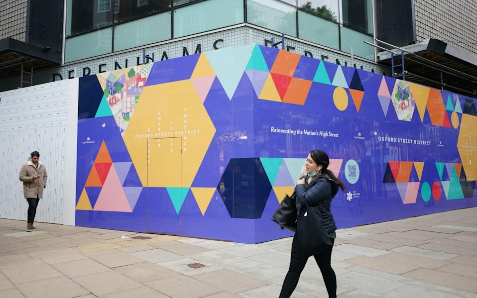 People walk past the boarded up former Debenhams flag-ship store in Oxford Street - Yui Mok/PA