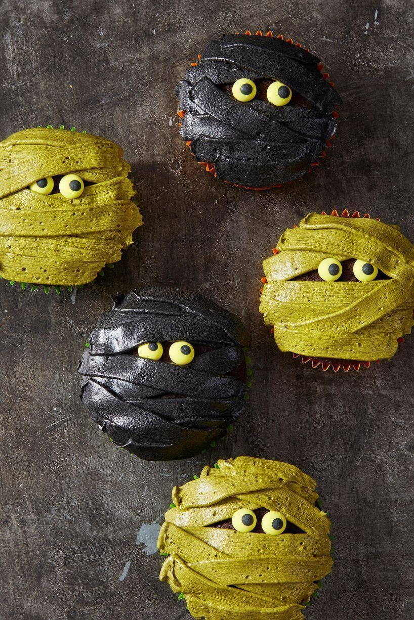 """<p>Your guests will be dying to unwrap one of these ghoulish treats.</p><p>Get the recipe from <a href=""""https://www.goodhousekeeping.com/food-recipes/party-ideas/a28593338/mummy-cupcakes-recipe/"""" rel=""""nofollow noopener"""" target=""""_blank"""" data-ylk=""""slk:Good Housekeeping"""" class=""""link rapid-noclick-resp"""">Good Housekeeping</a>.</p>"""