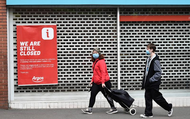 Members of the public walk past a closed shop in Leicester city centre - AP
