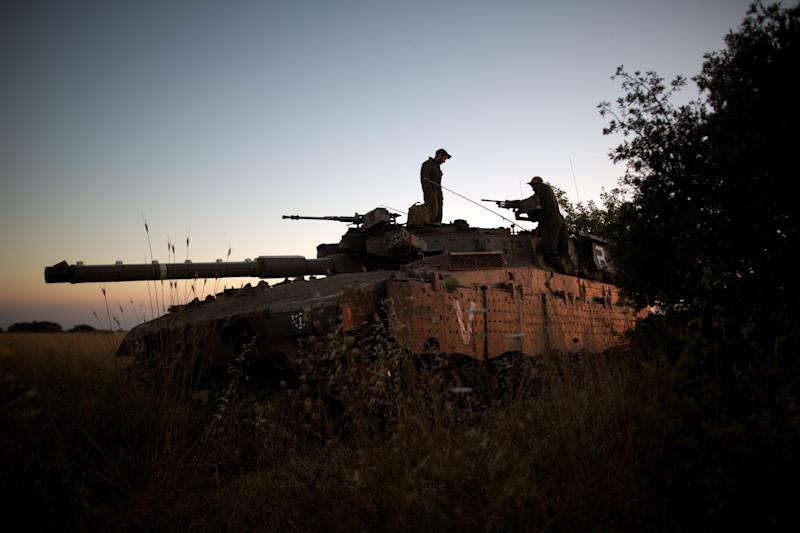 Israeli soldiers are seen on their Merkava tank positioned near the Quneitra checkpoint on the border with Syria in the Israeli-annexed Golan Heights, on June 22, 2014
