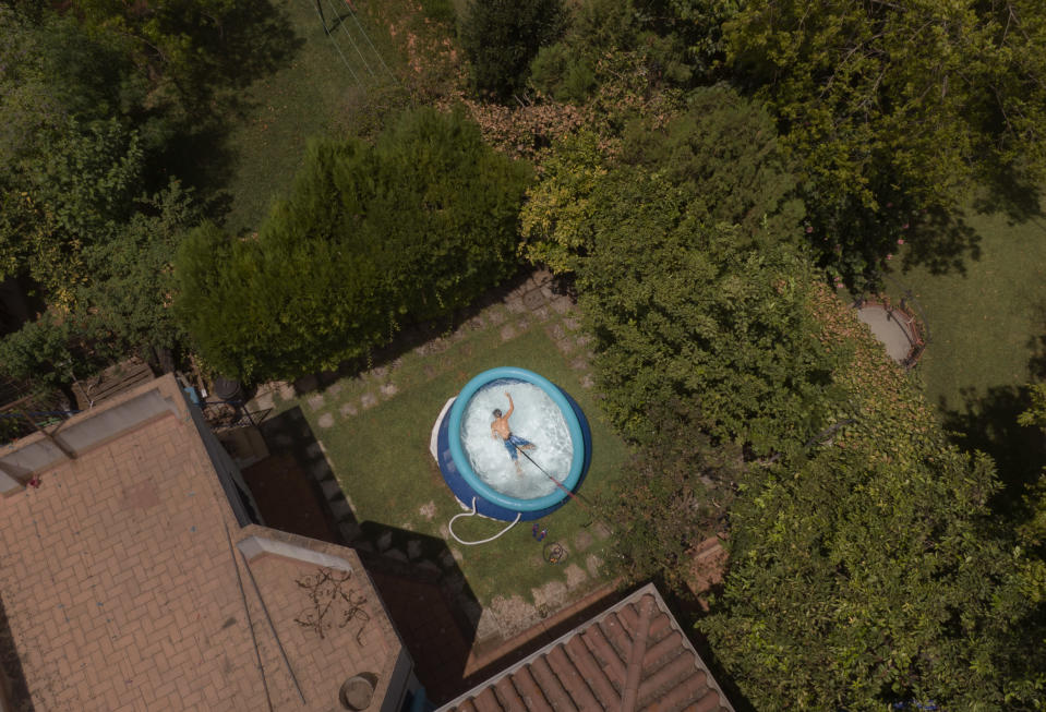"Ricardo D'hont swims in a neighbors plastic portable pool in Seville, Spain on Aug.11, 2020. The owners of the pool said that ""Due to the coronavirus we couldn't go to the beach or to other pools. If we hadn't been in pandemic we would never bought a plastic pool"". (AP Photo/ Laura Leon)"