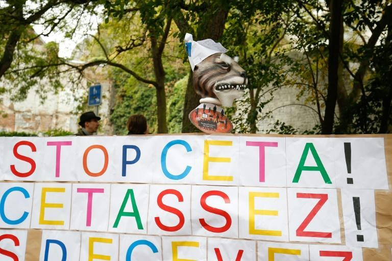 A placard reads 'Stop CETA - it's enough' during a protest against the CETA trade deal in front the Walloon parliament in Namur, Belgium on October 21, 2016