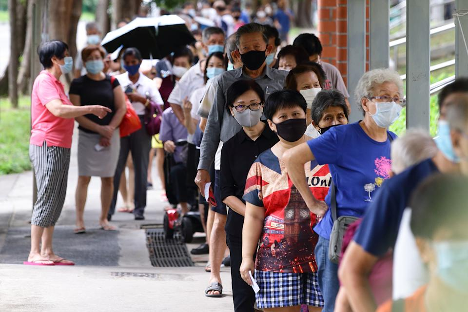 Voters wearing protective masks queue to enter a polling station during the general election on July 10, 2020 in Singapore. (Photo by Suhaimi Abdullah/Getty Images)