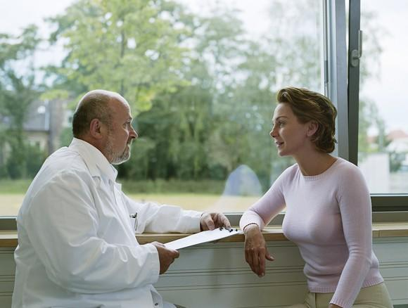 Doctor talking to a female patient in front of a window.