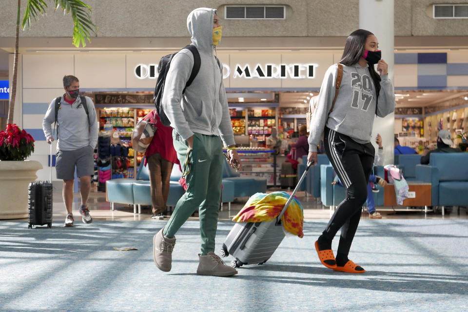 Holiday travelers make their way through Orlando International Airport Tuesday, Nov. 24, 2020, in Orlando, Fla. (AP Photo/John Raoux)