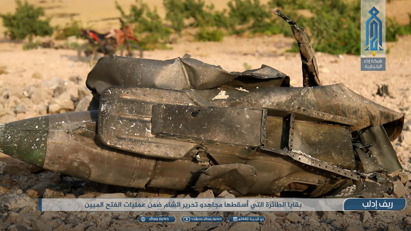 "This photo provided by the Ibaa News Agency, the media arm of al-Qaida's branch in Syria, purports to show part of a Syrian warplane that was shot down by rebel fighters over Idlib province in Syria, Wednesday, Aug 14, 2019. The Britain-based Syrian Observatory for Human Rights, a war monitor, said the warplane was shot down on the southern edge of Idlib province, while activist Taher al-Omar who has close links with militants said it was a Russian-made SU-22. The caption in Arabic reads:  ""The remains of the warplane that was shot down by holy warriors of Hayat Tahrir al-Sham as part of the Great Conquest operations."" (Ibaa News Agency via AP)"